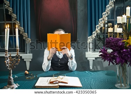 Man with a book in hands at the table in his study