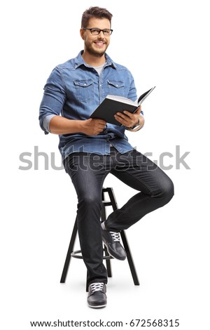 Man with a book sitting on a chair and looking at the camera isolated on white background