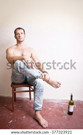 Man with a bottle of wine sitting on a chair - stock photo