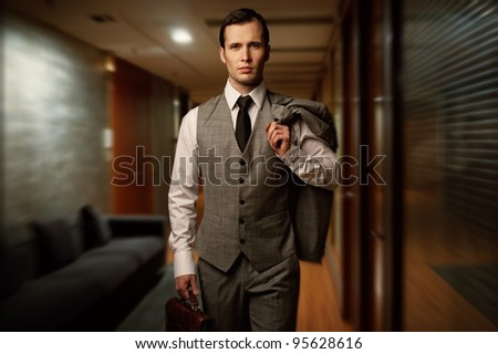Man with a briefcase in a hotel hallway. - stock photo