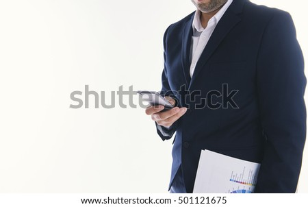 Man with a business report typing at his smartphone.