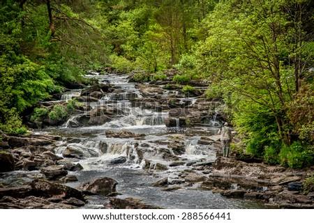 Man with a camera on the falls of Dochart in Killin, Scotland. - stock photo