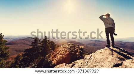 Man with a camera standing on at the edge of a cliff overlooking the mountains