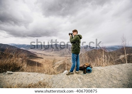 man with a camera stay on the background of mountains - stock photo