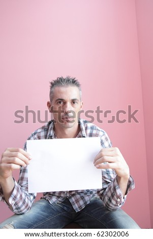 man with a checked shirt holding a blank billboard - stock photo