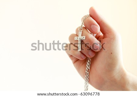 man with a cross between the fingers - stock photo