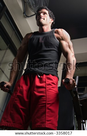 Man, with a determined expression on his face, exercising his arm muscles on an exercise machine in a fitness center. - stock photo