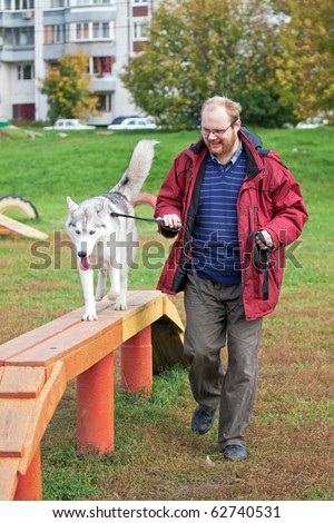 Man with a dog breed Siberian Husky - stock photo