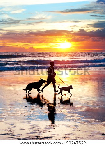 Man with a dogs running on the beach at sunset. Bali island, Indonesia  - stock photo