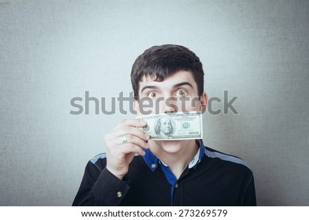 Man with a 100 dollar banknote on his mouth. on a gray background. - stock photo