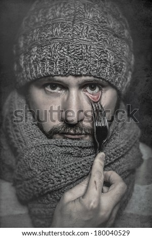 man with a fork in his eye, concept danger, risk - stock photo