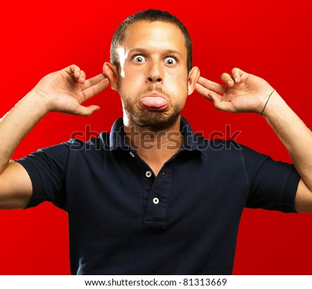 man with a funny face on a red background - stock photo