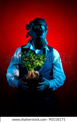 Man with a gas mask holding a tree - stock photo