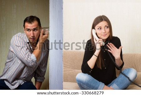 Man with a glass listening to the girl's phone conversation through the wall - stock photo