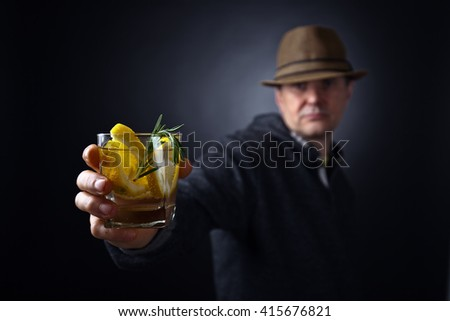 man with a glass of lemon drink , focus on foreground