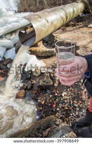 Man with a glass of water in his hand stand near a sewer from which water flows into the river in the spring sunny day - stock photo