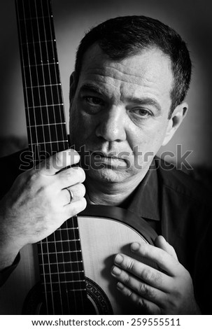 Man with a guitar. Black and white portrait - stock photo