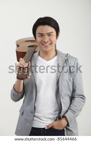 man With a guitar on his shoulder - stock photo