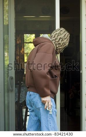 man with a gun breaking into a home - stock photo