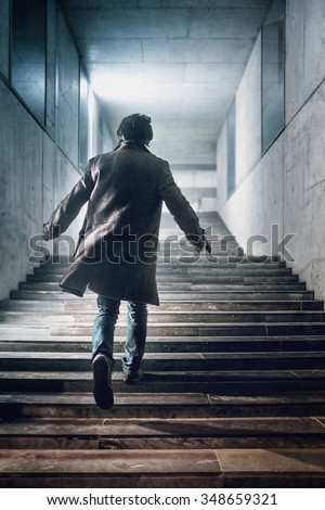 Man with a handgun running up a stairway in a modern building - stock photo