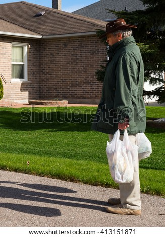 Man with a hat carrying shopping bags