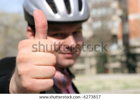 Man with a helmet holding thumb up - stock photo
