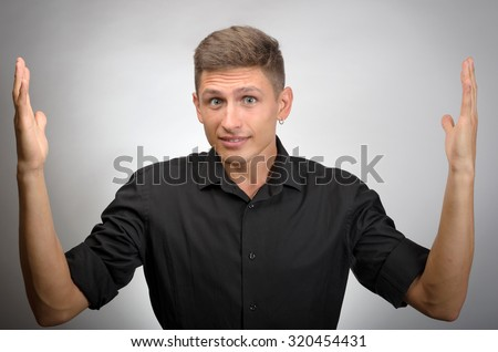 Man with a kind of uncomprehending opened his arms to the sides - stock photo
