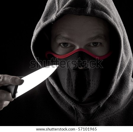 Man with a knife and mouth cover - stock photo