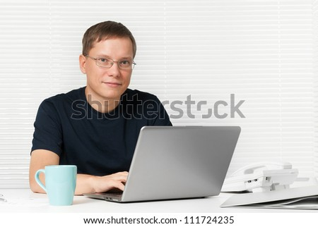 man with a laptop at the desk - stock photo