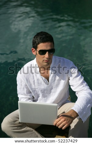 Man with a laptop computer at the sea