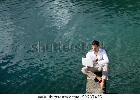 Man with a laptop computer at the sea - stock photo