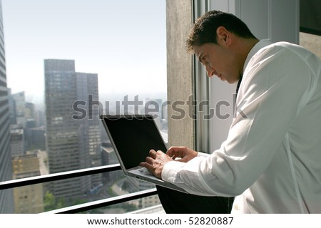 Man with a laptop computer in front of a window - stock photo