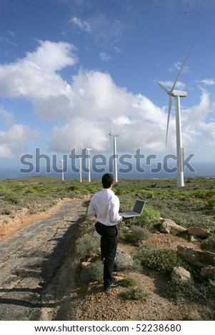 man with a laptop computer in front of wind turbines