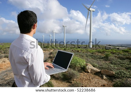man with a laptop computer in front of wind turbines - stock photo