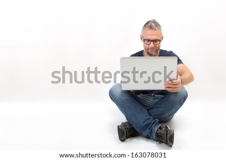 Man with a laptop - isolated sitting over a white background - stock photo