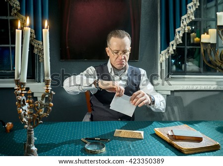 Man with a letter in hands at the table in his study