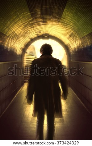 Man with a long coat walking away in a under passage to the light - stock photo