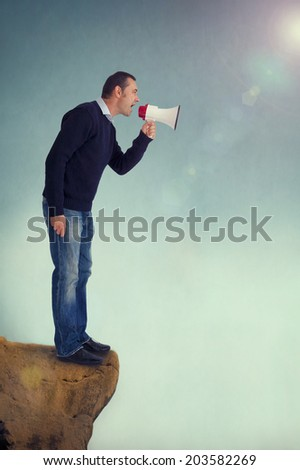 man with a loudhailer or megaphone shouting from edge of a cliff - stock photo