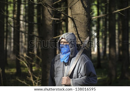 Man with a machete in the woods leaning against tree - stock photo