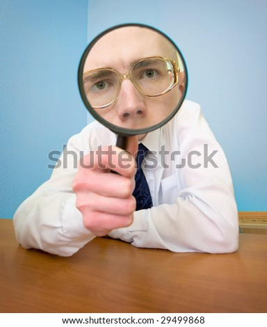 Man with a magnifier in a hand on a workplace - stock photo