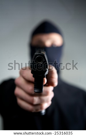 man with a mask a gun ready to use - stock photo