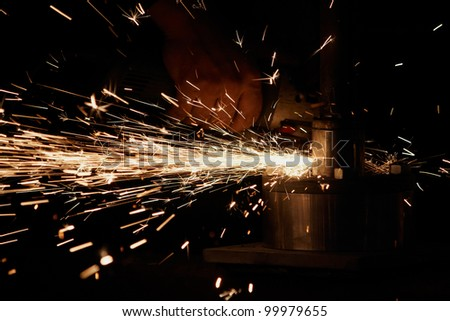 Man with a metal grinder grinding, sparks - stock photo