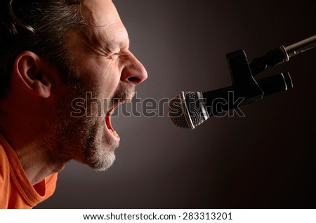 Man with a microphone in a studio - stock photo