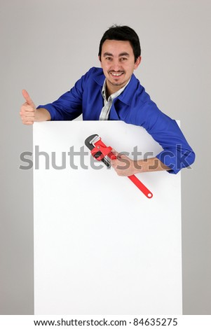 Man with a monkey wrench and a blank poster - stock photo