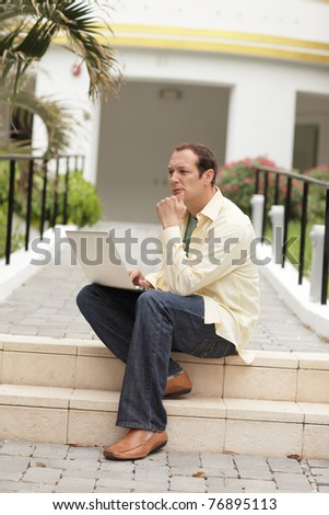 Man with a notebook computer sitting on the steps - stock photo