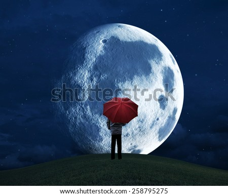 Man with a red umbrella standing on a hill at night and looking to the moon - stock photo