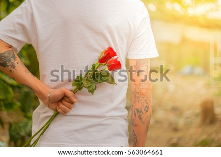 Man with a rose behind his back waiting for love girlfriend in Valentine's Day or anniversary  .