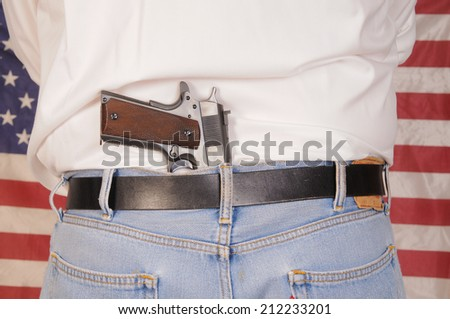 Man with a semi-automatic pistol stuck in his waistband in front of an American flag - stock photo