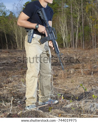 Man with a semi automatic rifle and handgun in a field