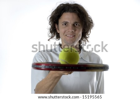 Man with a smile on his face holds a tennis racket and balances a tennis ball on top of it. Horizontally framed photograph - stock photo